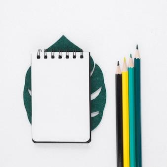 Плоский блокнот и карандаши