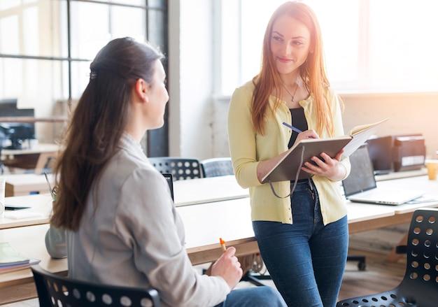 日記とオフィスで彼女の同僚を探しているペンを持つ女性の笑みを浮かべてください。