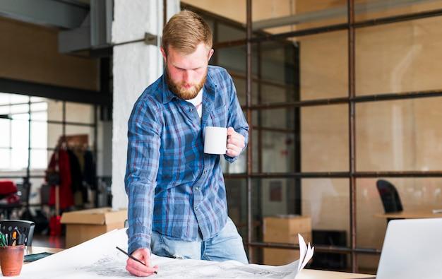 彼のオフィスでコーヒーカップを押しながらブループリントを描く男