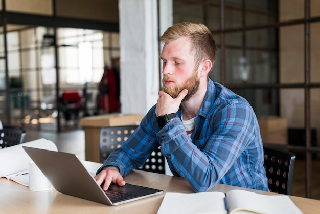 ラップトップを使用してオフィスに座っている若い男