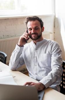 職場で携帯電話で話している若い男の笑みを浮かべてください。