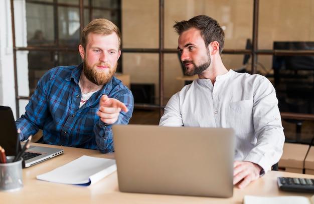 Человек, указывая пальцем на ноутбук своего коллеги на рабочем месте