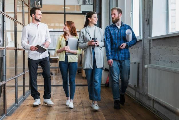 一緒に歩く若いビジネス同僚のグループ