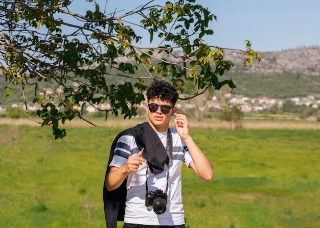 緑の風景の上に立ってカメラを持つ若い写真家