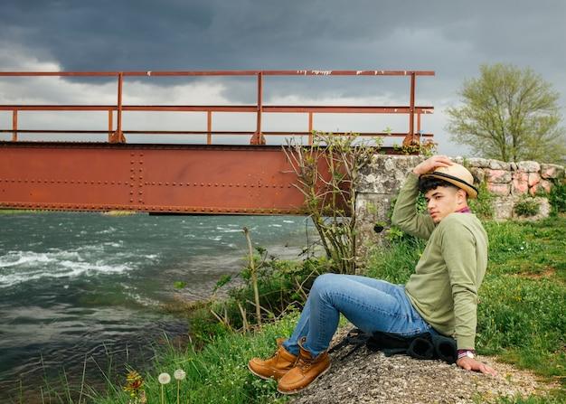 花の川のそばに座って帽子をかぶっている男