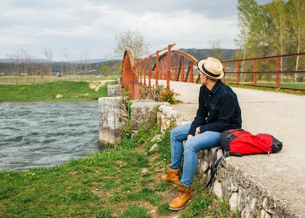 男は流れる川の土手銀行をリラックスします。