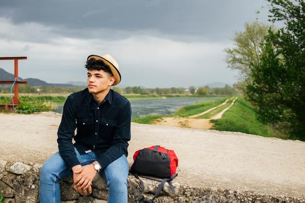 橋の上のバックパックと立地の帽子をかぶっている若い観光客