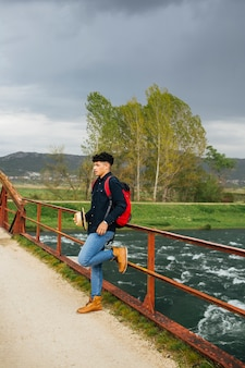 Стильный мужчина держит шляпу, опираясь на перила моста через реку
