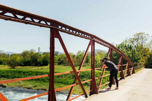 橋から流れる水の写真を撮る男