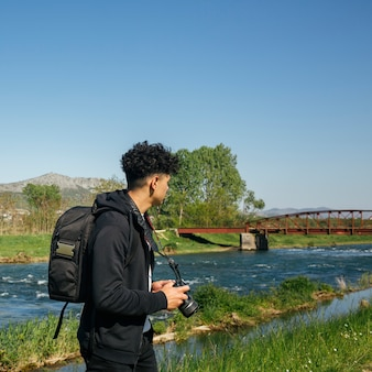 バックパックと美しい川の近くカメラハイキングを運ぶ男性カメラマン