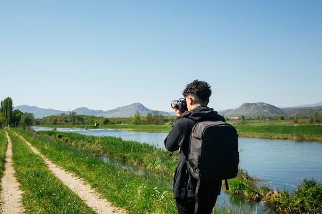 流れる川の写真を撮る若い写真家の背面図