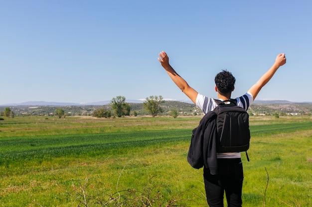 バックパックと美しい緑の風景の近くに立っている人の後姿