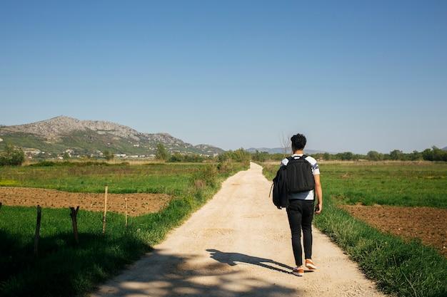 バックパックを運ぶと自然歩道の上を歩く若い男