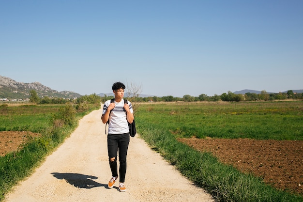 バックパックを運ぶ未舗装の道路の上を歩く若いハンサムな男