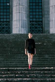 Портрет модной молодой женщины, стоя на лестнице, глядя на камеру