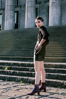 Привлекательная молодая женщина позирует перед лестницей с руки на бедрах