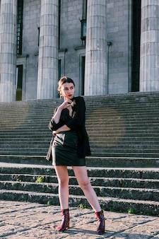 Модная молодая женщина, стоя перед лестницей