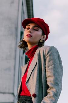 カメラを見て赤い帽子を持つファッショナブルな若い女性