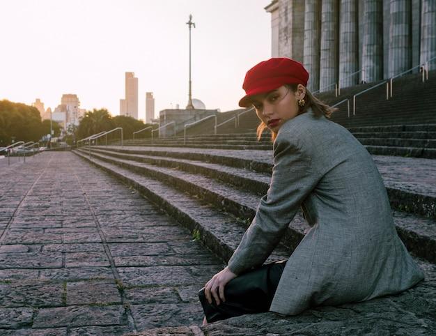 肩越しに見ている階段のそばに座っているトレンディな若い女性