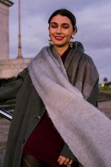 カメラを見て彼女の首の周りの長いスカーフを持つ美しい若い女性の笑みを浮かべてください。