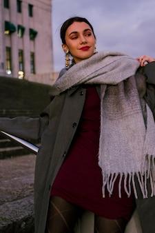 ぶら下がっている黄金のイヤリングを身に着けている近く彼女の周りのウールのスカーフを持つスタイリッシュな若い女性