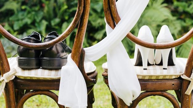 公園の木の椅子の上の結婚式の靴のペア
