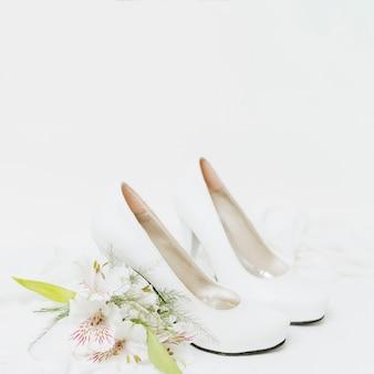 白い背景で隔離のハイヒールの結婚式のペアの近くのペルーのユリの花束