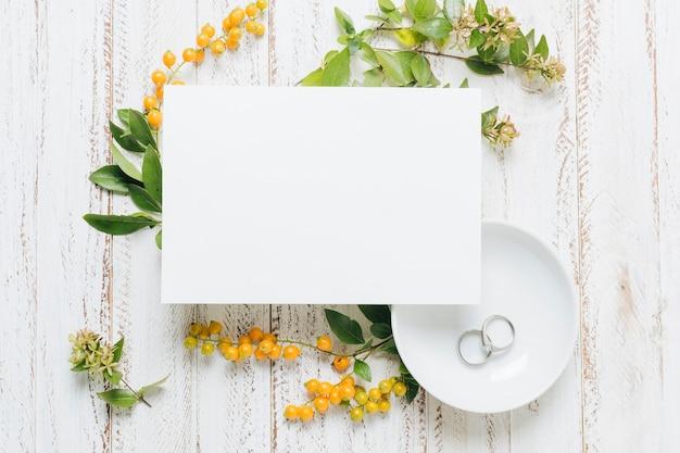 花と白い空白のウェディングカード。黄色の果実と木製の背景に結婚指輪