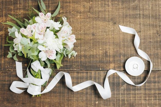 木製の机の上の皿の上の結婚指輪と白いリボンと花の花束