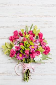カラフルな花の花束は木製の机の上のピンクのリボンと結ばれる