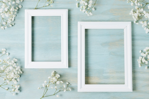 青いテクスチャ背景に空の白い木製フレームの周りの白い赤ちゃんの息の花
