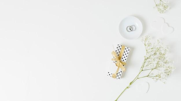 Обручальные кольца на тарелке рядом с цветочками и обернутой подарочной коробкой на белом фоне