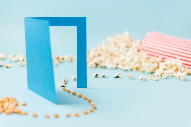 青い背景にポップコーンになって青い紙の戸口を通って行くコーンの種子