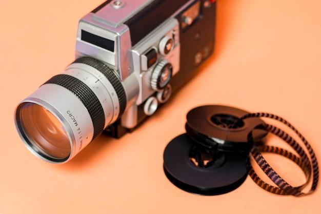 桃色の背景にフィルムストリップのビデオカメラ