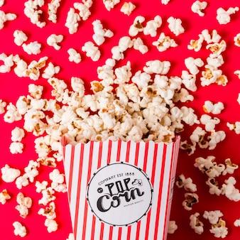 Поднятый вид попкорна, пролитого из полосатой коробки на красном фоне