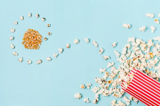 曲がったポップコーンとポップコーンの種子が青色の背景にフロントボックスをこぼした