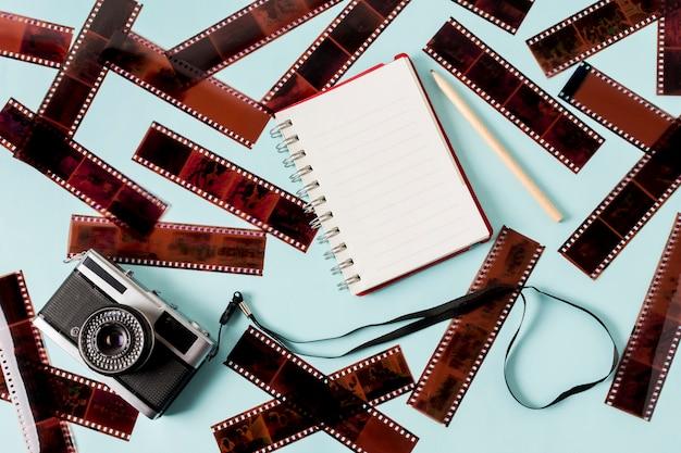 空白のスパイラルメモ帳。鉛筆と青い背景にネガティブストライプのカメラ