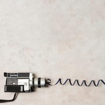 灰色のコンクリートの背景に渦巻き模様のフィルムストライプとビデオカメラの俯瞰