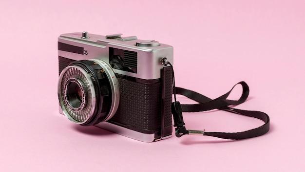 Старинный фотоаппарат на розовом фоне