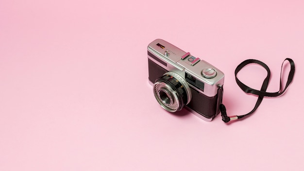 ピンクの背景にレトロなスタイルのカメラ