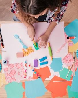 紙の上のカラフルな粘土を切る女性のトップビュー