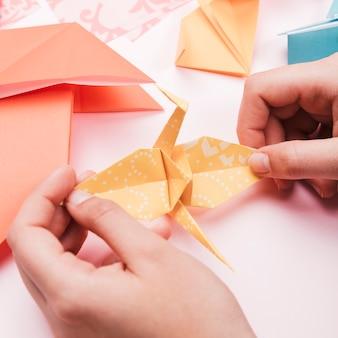 折り紙紙の鳥を持っているアーティストの手の高角度のビュー
