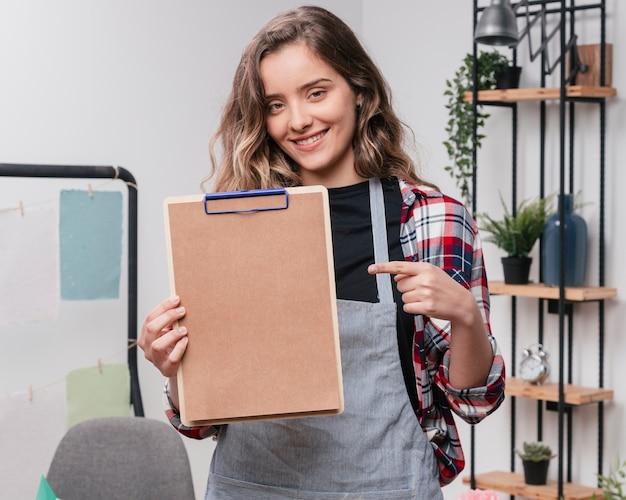 Молодая усмехаясь женщина указывая указательный палец на доску сзажимом для бумаги
