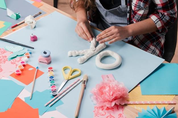 机の上の白い粘土で手紙を作る女性アーティストの高角度のビュー