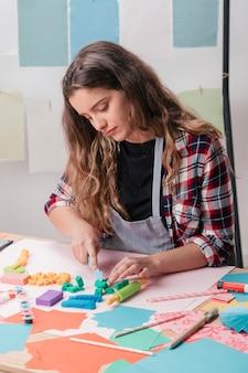 テーブルの上の粘土カッターで美しい若い女性切削粘土