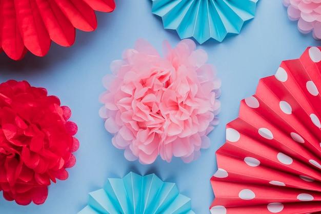 Поддельные красивые декоративные бумажные цветы оригами на синей поверхности