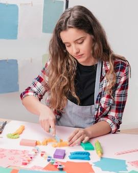 若い女性の机の上の粘土カッターを使用して粘土を切る
