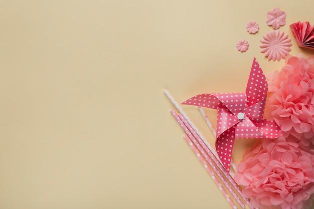 クリエイティブ風車。紙の花とベージュの表面上のわら