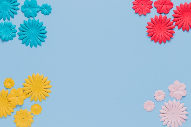青い背景の隅にカラフルな装飾的な花の切り欠き