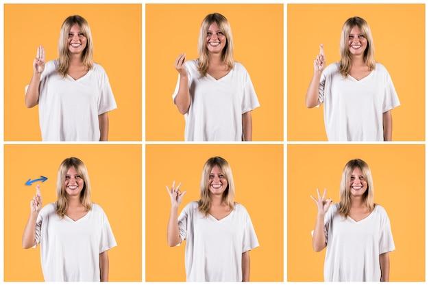 Комплект счастливой женщины показывая глухой знак против желтой стены